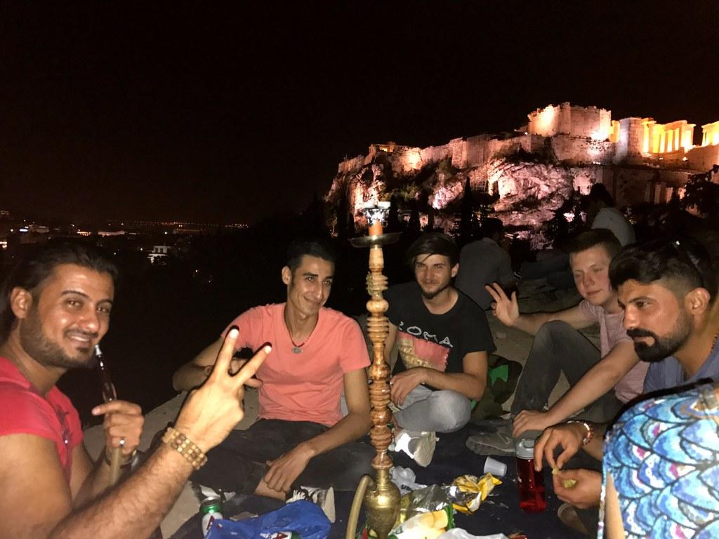 syarian and iraqi refuges smoking shisha in front of the acropolis of athens