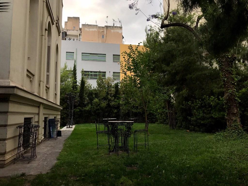 metal table and chairs in a grass houseyard in athens