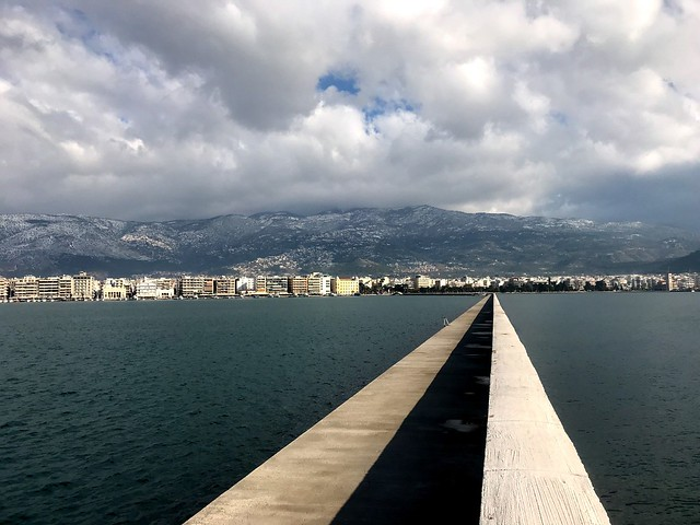 volos city and snow-clad mount pelion in winter from long pier