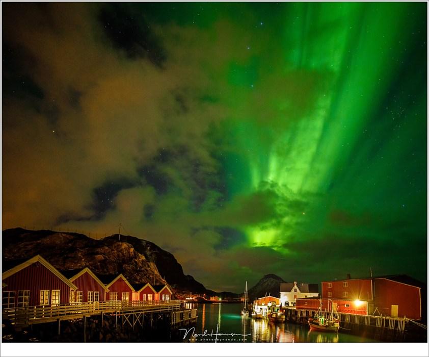 Het groene licht schijnt door tussen de bewolking door, boven de rorbuer van Mortsund (16mm | ISO6400 | f/2,8 | t=5sec), Lofoten in de nacht