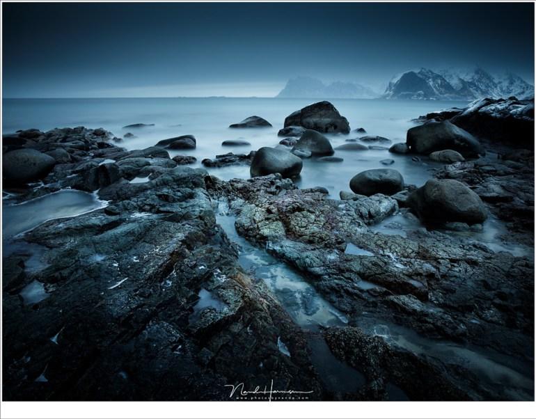 Het strand van Myland met een ogenschijnlijke rustige, vlakke zee. In de verte doemen de bergtoppen bij Uttakleiv en Haukland op. (24mm   ISO100   f/16   240sec met 10 stops ND)