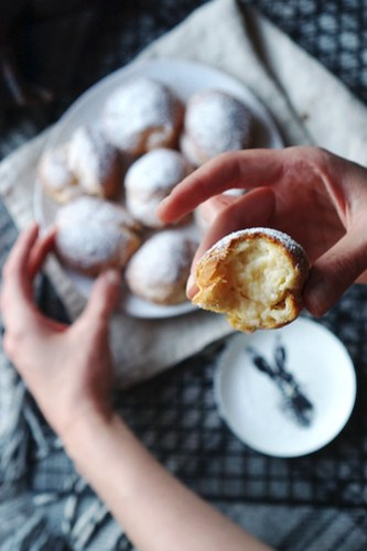 Gluten free cream puffs filled with pastry cream and covered in a dusting of icing sugar.