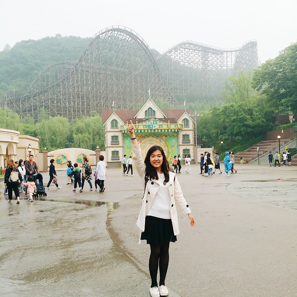 a girl in front of the wooden rollercoaster of Everland theme park