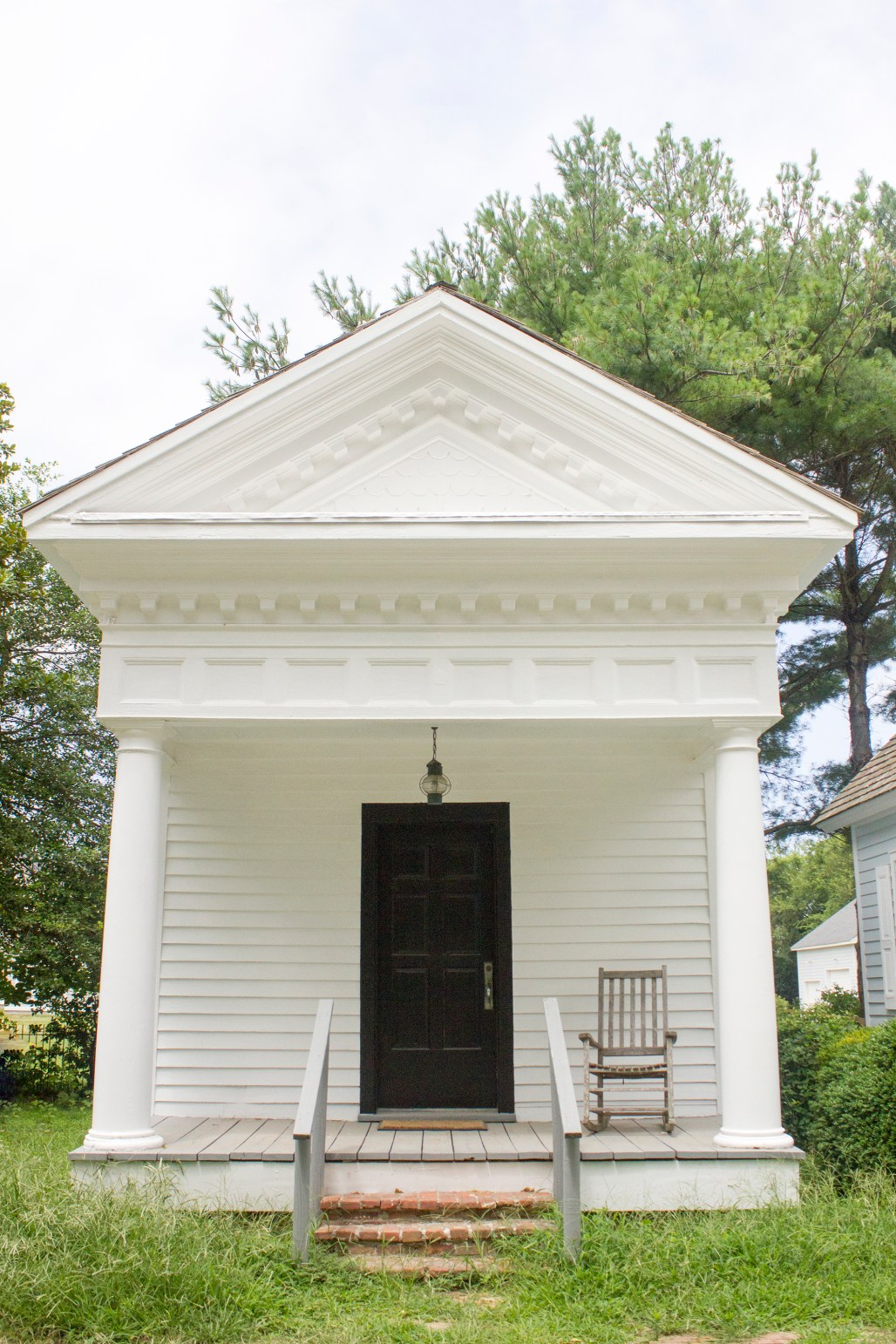The front of the doctor's office, with a small porch and rocking chair.