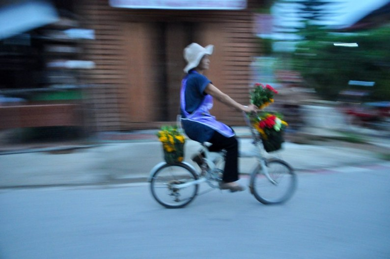 A woman sells flowers as offerings for the monks of Chiang Khan, Thailand, March 2015.