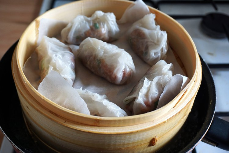 Gluten free steamed Chinese rice wrap dumplings in a bamboo steamer