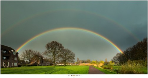 Een dubbele regenboog tegen een donkere hemel vol met regen. Alsof de natuur het goed wil maken voor een onstuimige dag vol regenbuien.