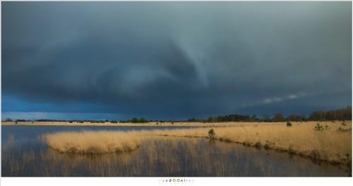 Ergens aan de horizon, onder die donkere wolken, valt de regen in stromen naar beneden.