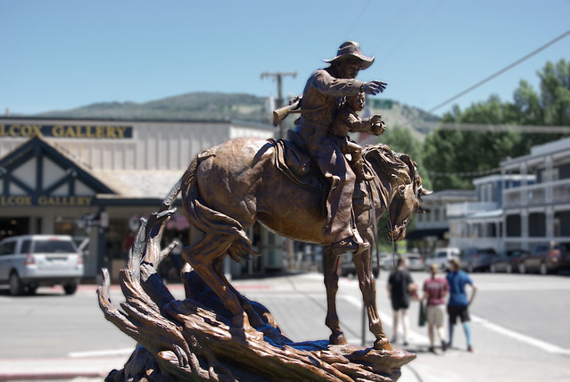 """Memories"" -- sculpture by Ken Payne. bronze sculpture of a Cowboy and Young Boy on a Horse, outside of Mountain Trails Galleries on corner of Center and Deloney in Jackson, Wyoming"