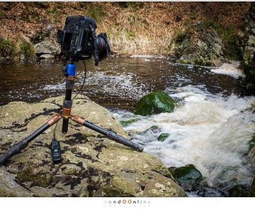 Omringt door wild stromend water, balancerend op een rots, aan het fotograferen met filters en lange sluitertijden.