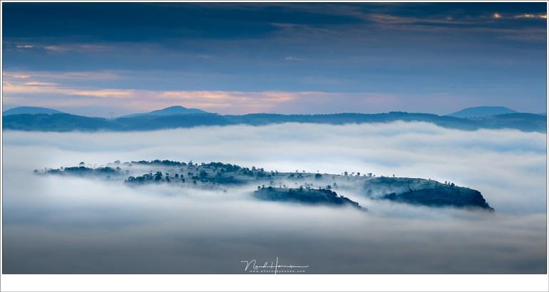 Niet alleen de burcht van Polignac steekt boven de wolken uit, her en der breekt de top van een heuvel door de mist, als eilanden waar vingers van mist overheen kruipen. (EOS M50 + EF-M18-150mm @ 66mm | ISO125 | f/8 | 1/125)