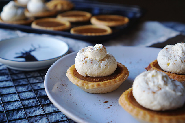 Homemade mini gluten free pumpkin pies with hazelnut flavoured whipped cream and a sprinkle of cinnamon