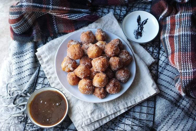 Plate of gluten free churro donut holes rolled in cinnamon sugar with a homemade caramel dipping sauce. | Featuring H&M Home small rabbit plate.