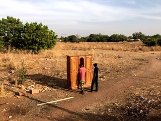 two men opening up a wardrobe left in the middle of a field in tambacounda, senegal