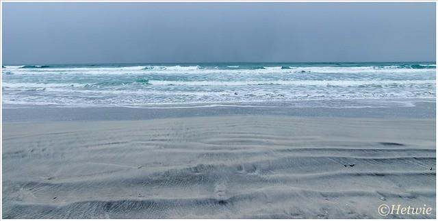 Golven in het zand en het water.