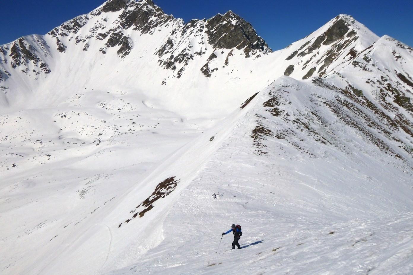 Výztup ze sedla absolvujeme pěšky bez lyží. Vpravo hřeben na Mödringkogel, uprostřed a vlevo vyhlášený Gamskogelgrat.