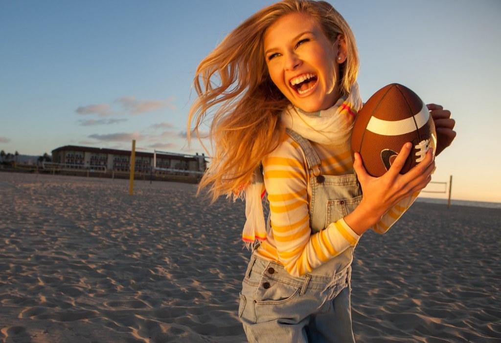 Imagen gratis de una chica con un balón de rugby en la playa
