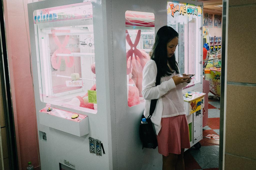 Una chica juega con su móvil en la puerta de una sala de recreativas en Taipei City Mall