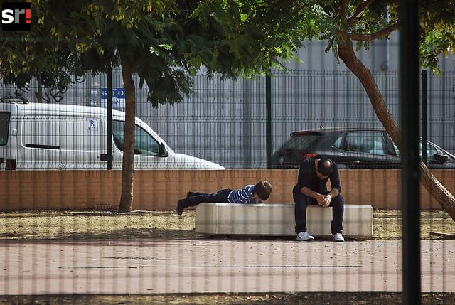 Un padre cabizbajo, junto a su hijo, en un parque de Tres Barrios