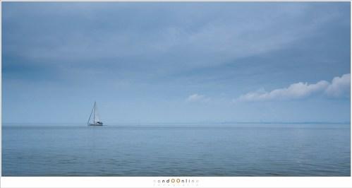 Een tikkeltje blauw in de lucht, een kalme zee, het vredig voorbij varen van een zeilboot, in stilte.