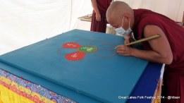 Biksu sedang melakukan demo menggambar dengan pasir.