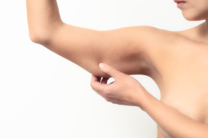 Woman testing the flabby muscle under her arm pulling it down with her hand as she checks for muscle tone or weight gain