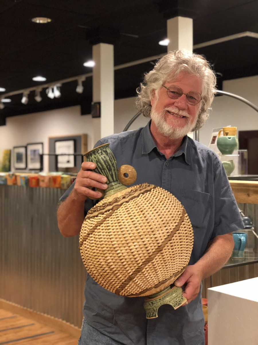 Ceramic artist Stephen Kostyshyn holding a ceramic basket bottle