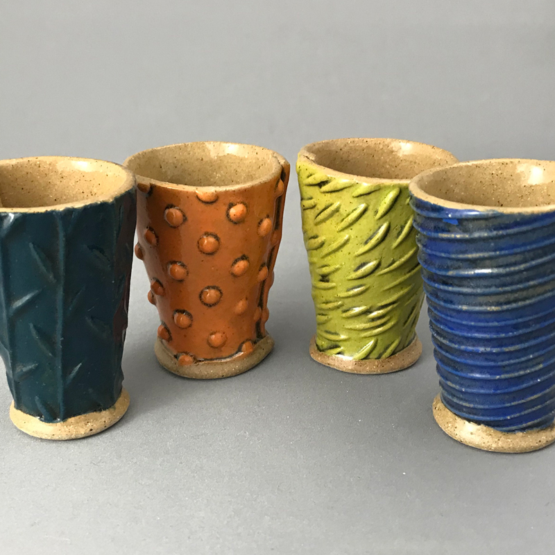 4 handmade 2oz shot glasses in a line