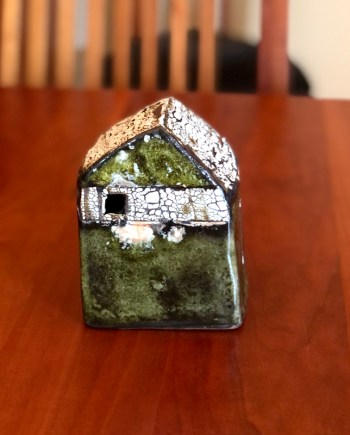 small decorative ceramic cottage on a table