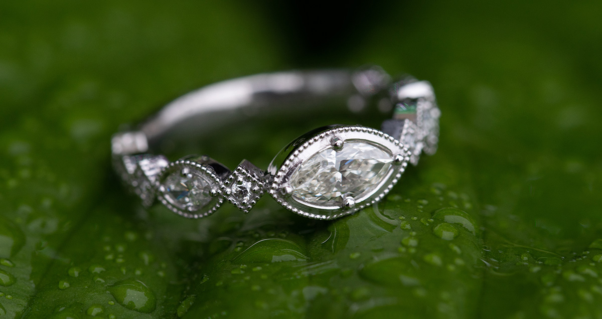 a white gold ring with a marquise diamond set sideways in the center on a wet leaf