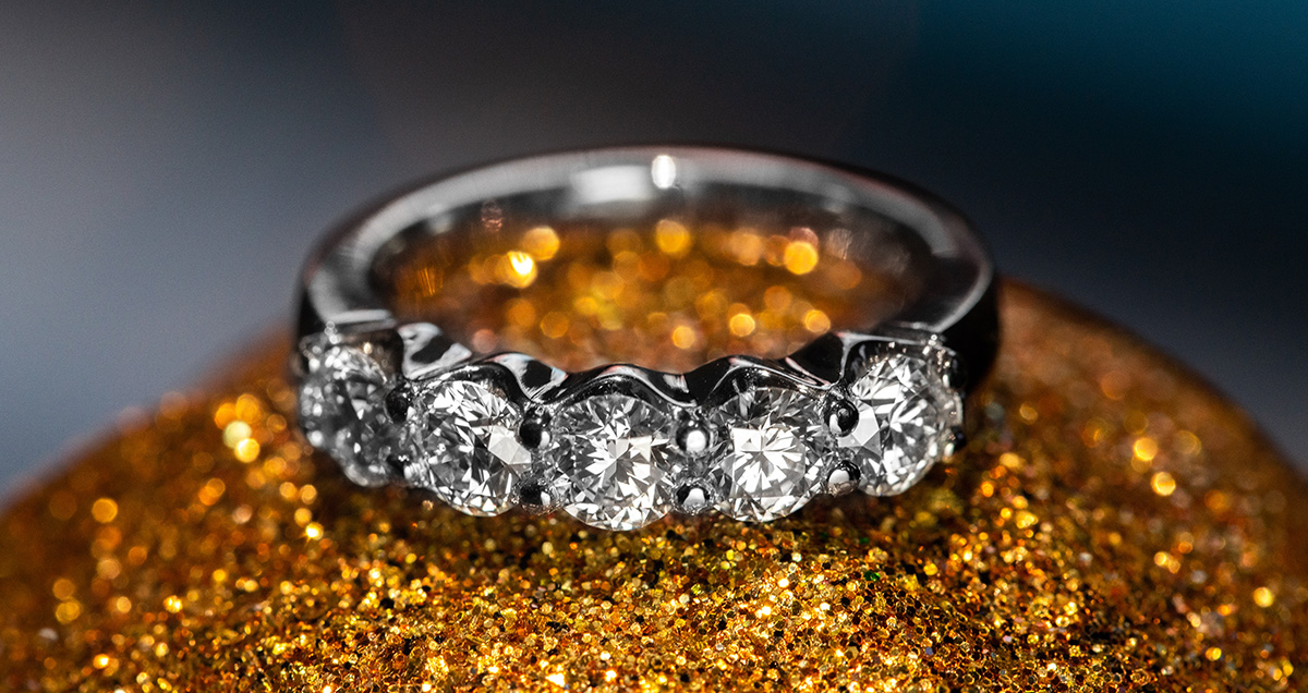 white gold custom diamond band with 7 diamonds on a glittery background