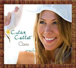 """Colbie Callait under a white sweater. There's a yellow flower with a brown stem. The words """"Colbie Caillat"""" are in teal, and the word """"coco"""" is in black. There is a brown border surrounding it."""