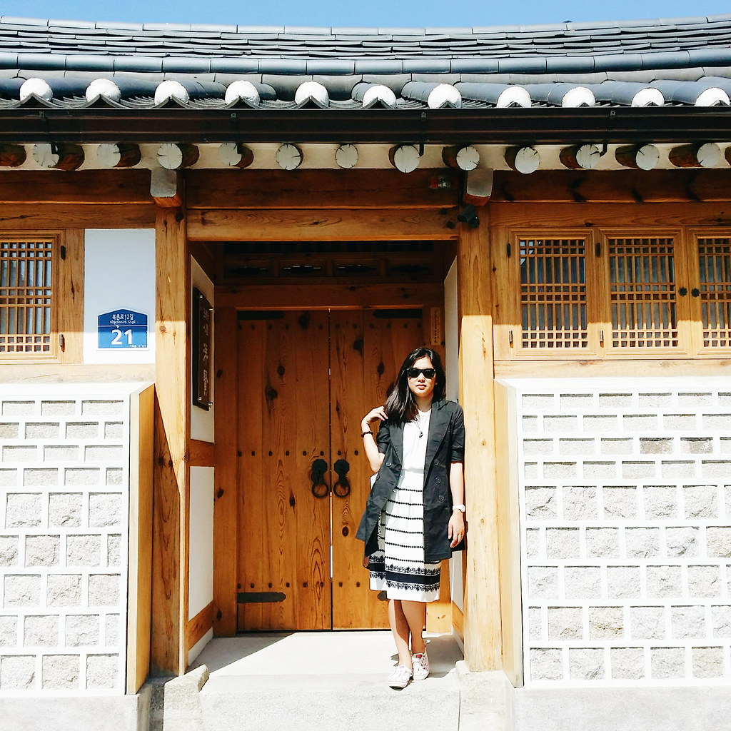 A girl in white dress and black coat standing in front of a door of a hanok in Bukchon Hanok Village