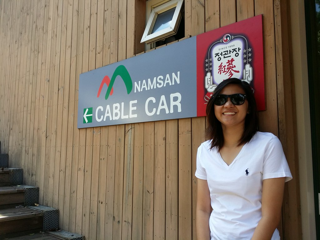 A girl posing in front of the Namsan Cable Car signage