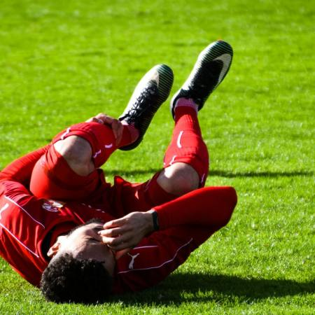 Soccer player suffering a sprain or strain.