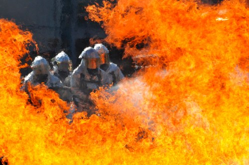 Florida and Virginia Guardsmen, firefighters extinguish a fire in a live-fire training simulator