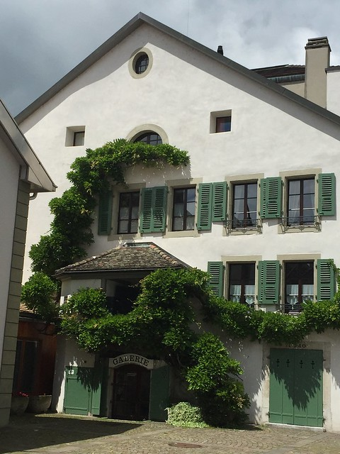 Nyon's main square: a typical local house with sloping roof, green wooden shutters and a climbing evergree.n. Nyon is the perfect kid-friendly trip from Geneva but also a pleasant stop without children