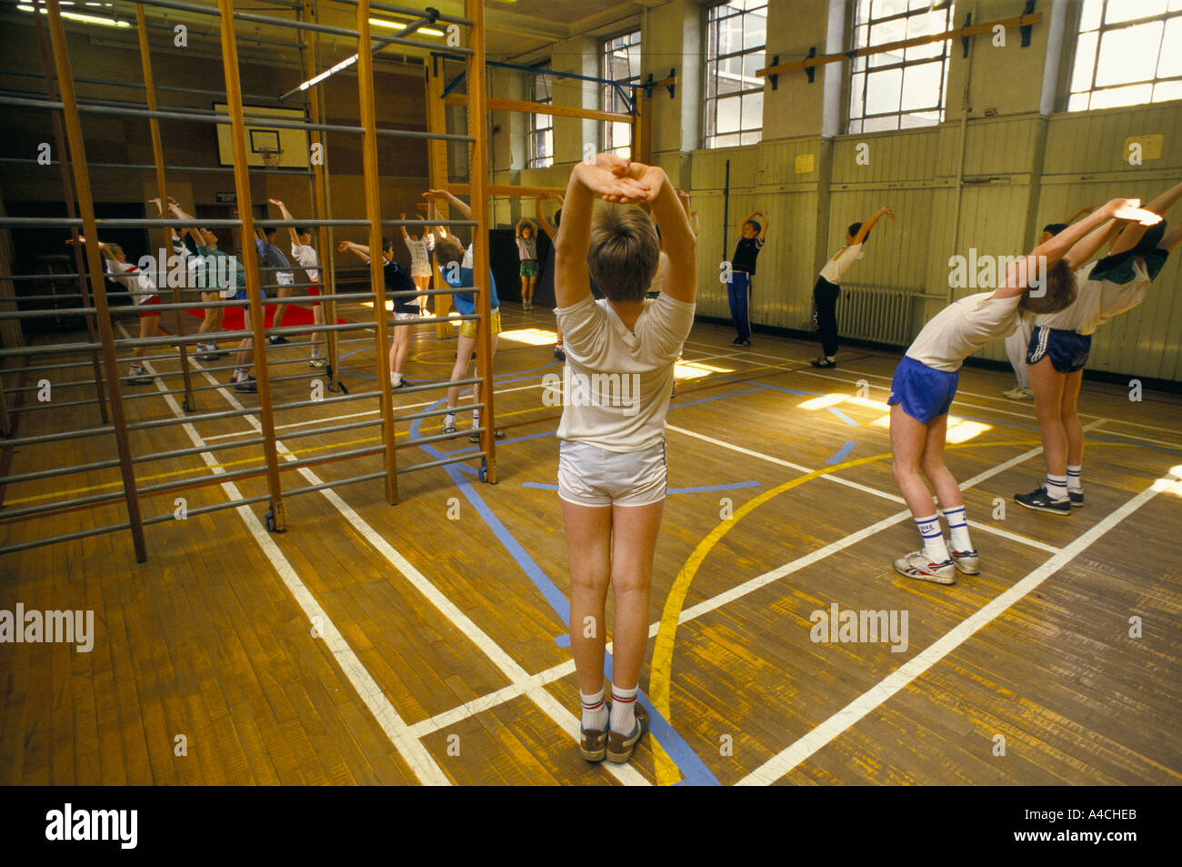 Pupils Doing Stretching Exercises During Gym Class In