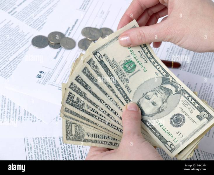 Closeup of female hands counting tax money over W 9 income tax forms     Closeup of female hands counting tax money over W 9 income tax forms