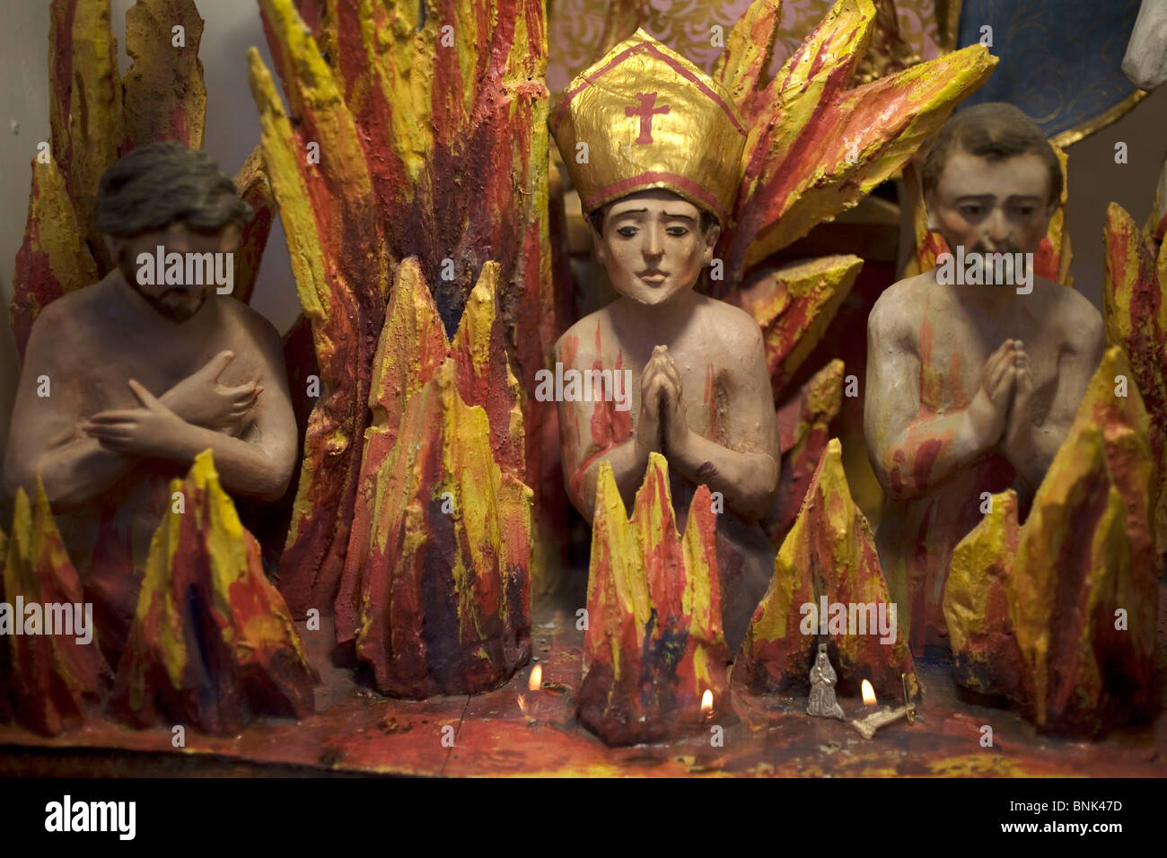 Sculptures of priests and a bishop burning in hell are displayed in a church of San Miguel de Allende, November Stock Photo