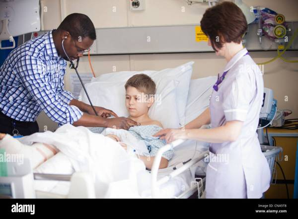A young boy is checked by a doctor and nurse on a children ...