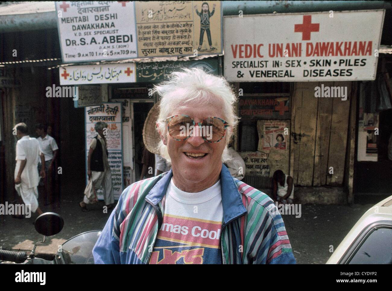 Sexual Abuse Scandal Sir Jimmy Savile, OBE pictured outside a Sex Clinic in Mumbai, India in 1992. While other passengers Stock Photo