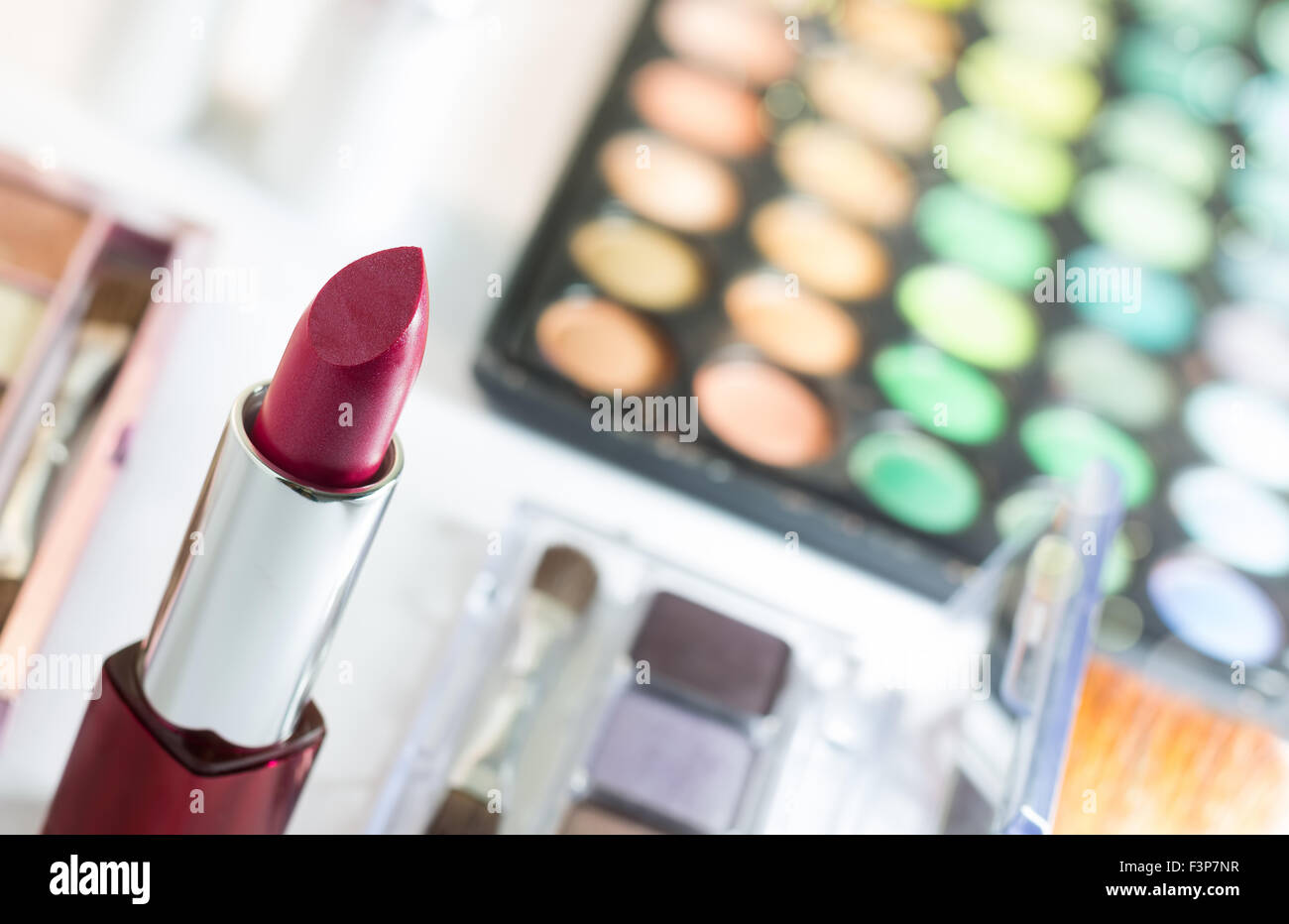 Red lipstick with blur cosmetics background such as makeup palette     Red lipstick with blur cosmetics background such as makeup palette and  blush on and negative space for word and text