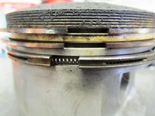 Rings In Grooves of Piston-Note Bottom Oil Control Ring Is Two Piece