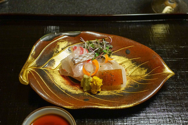 Sashimi of tai (red sea bream) and managatsuo (silver pomfret), ponzu jelly, wasabi, vinegared chrysanthemum petals, mixed sprouts, curled udo stalk and carrot