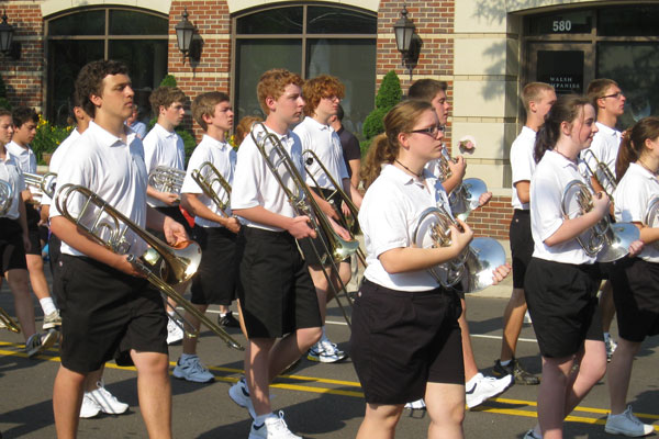 Plymouth-Canton Educational Park trumpet and trombone band members hold their instruments as they walk down Main Street