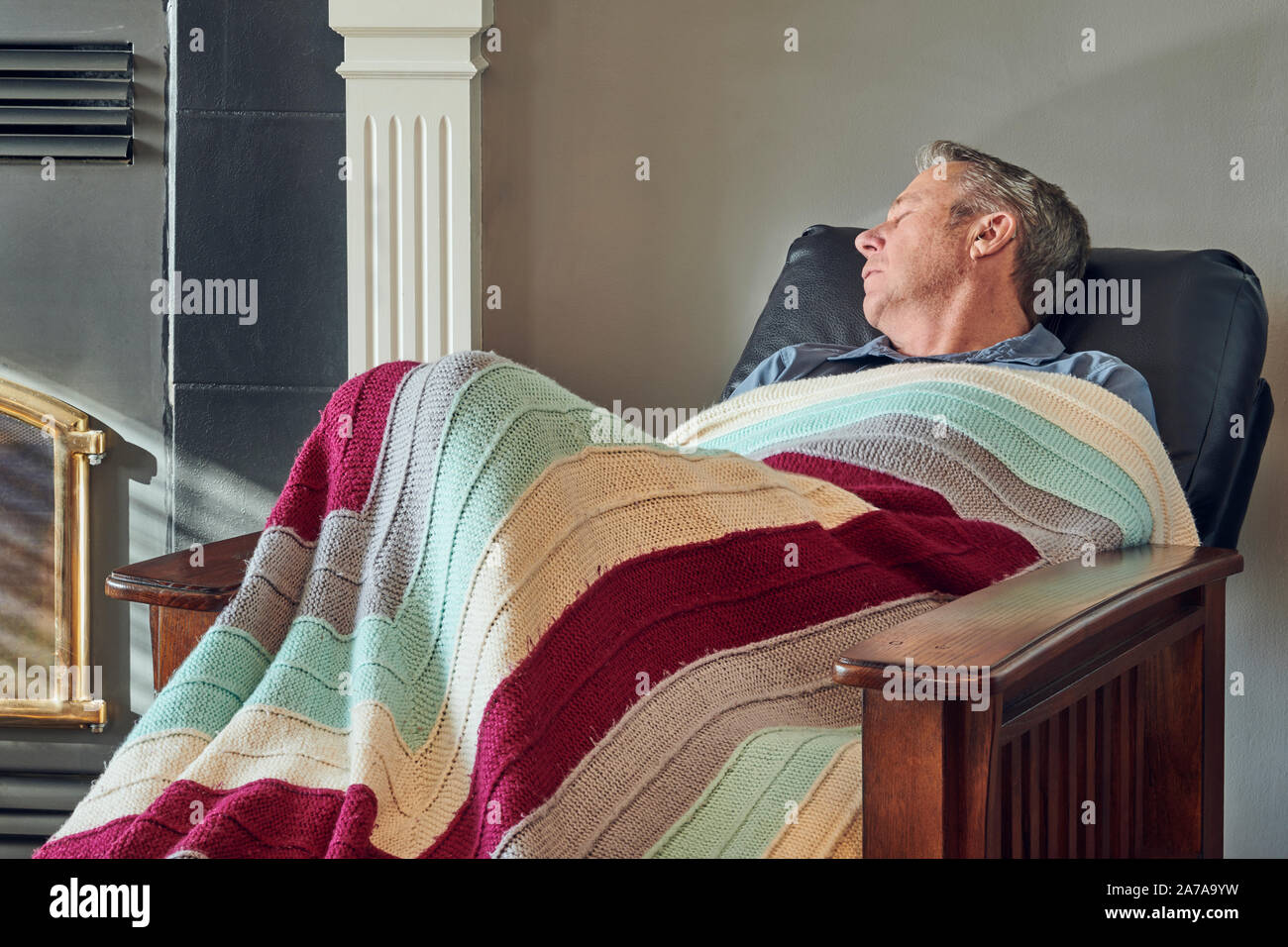 https www alamy com elderly man in recliner chair by the fireplace lit by sunlight coming through the window image331526941 html