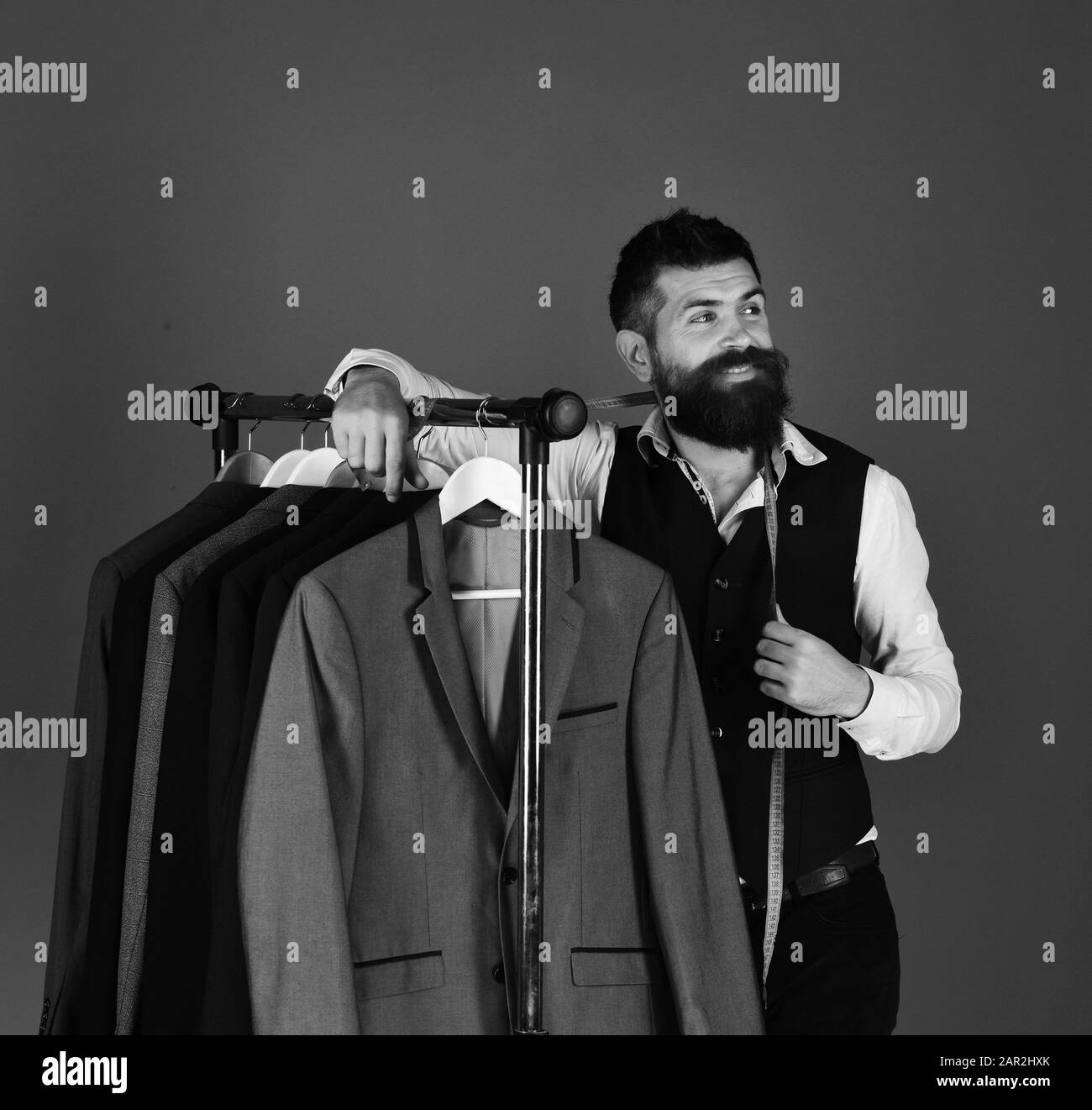 https www alamy com young tailor with tape measure near suit rack guy with beard and jackets on blue background tailoring and design concept image341192059 html