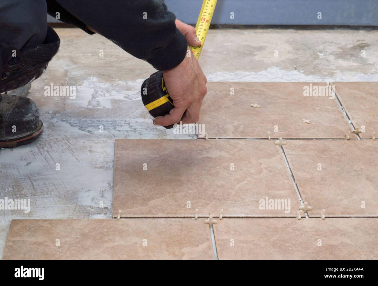 https www alamy com ceramic tiles are being put down by a contractor on a cement floor the contractor measures the area for the next tiles image346015386 html