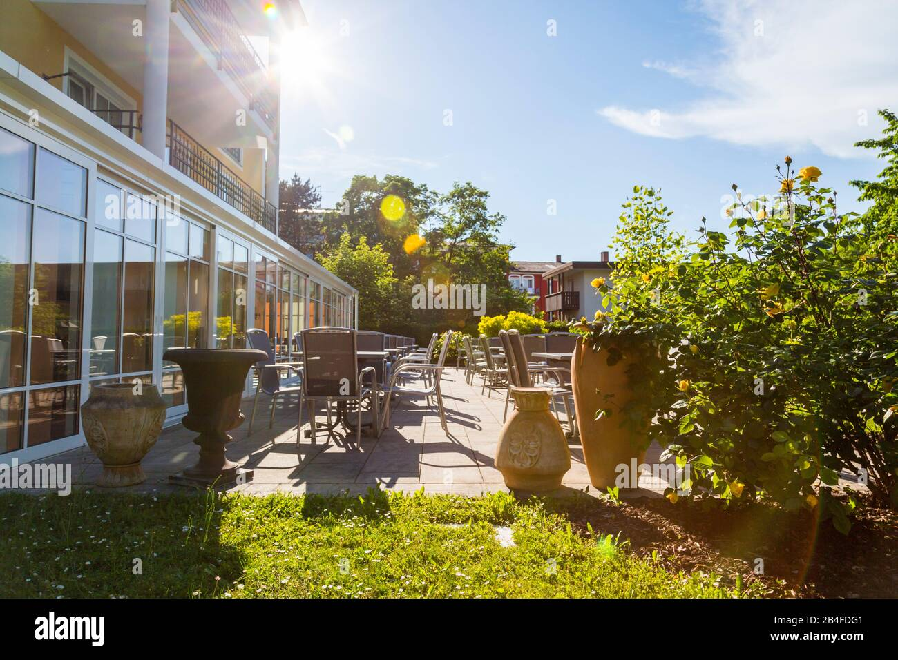 https www alamy com sun flare around the corner of a commercial glass fronted building over an outdoor patio with restaurant tables and chairs surrounded by green plants in bad fussing lower bavaria germany in summer image347005905 html